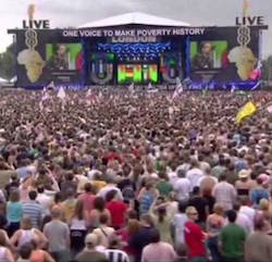 "A stage in Hyde Park, London, with audience in the foreground. The stage features two live 8 logos of guitars with bodies shaped like Africa with the slogan ""One voice to make poverty history"" across the top of the stage."