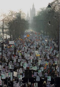 "Picture of a demonstration passing along Victoria Embankment in London in 2003. There is a slight mist which dims the view of the clock tower of Parliament in the distance. There are trees on either side of the road and the river Thames is on the left. The demonstrators are holding banners, chiefly saying ""Not in My Name"" and ""Don't Attack Iraq""."
