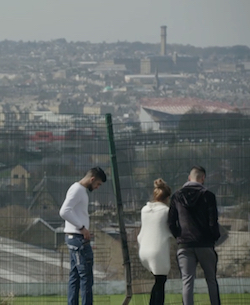 A picture of Mehreen Baig and two Asian men looking at a view of Bradford through a fence.