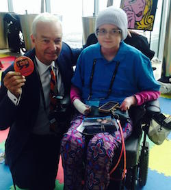 Picture of Lucy Glennon, a young white woman sitting in a wheelchair wearing a light grey wooly hat, a blue shirt with a pink top underneath, and pink and blue patterned trousers with a white dressing on her right forearm and hand, next to Jon Snow, a middle-aged white man with white hair, wearing a dark coloured suit with an orange tie, and an 'I can' badge in his hand