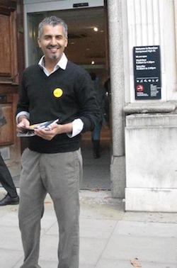 Picture of Maajid Nawaz, a middle-aged South Asian man, standing outside a branch of Barclays Bank with a yellow circular badge on his black jacket and leaflets in his hand