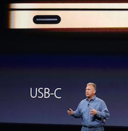 Picture of a white man wearing a blue shirt, and behind him a picture of the side of a new MacBook with a gold finish, showing one port, with the letters 'USB-C' on the screen below it