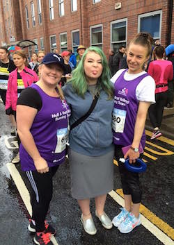"Picture of Maisie Shaw, a white girl in her early teens with green dyed hair, wearing a blue jumper and grey dress or skirt to below the knee, flanked by two white women with purple running T-shirts bearing the National Autistic Society logo and the words ""Hull and East Riding Running Team"""