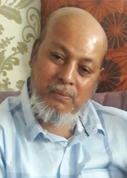 Picture of Makram Ali, a 51-year-old South Asian man with a bald head and a white beard, wearing a pale blue shirt.