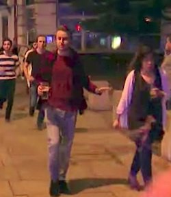 A group of people running away from something on a London street at night. There is a man at the front who is running with a pint of beer in his hand.