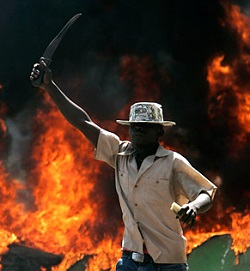 Picture of a black man holding a machete, standing in front of a burning building.