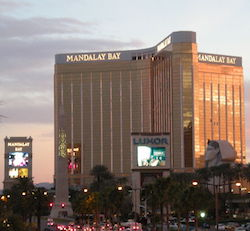 "A picture of the Mandalay Bay hotel, a tower block with three 'wings' coming out of a central point, illuminated by the sun, with the name ""Mandalay Bay"" in capital letters at the top of each wing. A replica of the Egyptian Sphinx stands in front of one of the wings and an obelisk and a video billboard with ""Luxor"" on them are also in the foreground, where there are palm trees, streets and traffic."