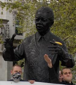 A bronze statue of Nelson Mandela, which has had a banana placed in its left hand. Two young white men, one with his face covered in a grey and black scarf, are standing at its feet.