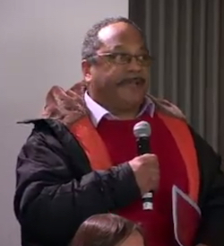 Picture of Marc Wadsworth, a middle aged, portly Black man with a receding hairline, wearing a red jumper with a black jacket over it, holding a microphone. The forehead of a white woman in the audience can be seen at the bottom.