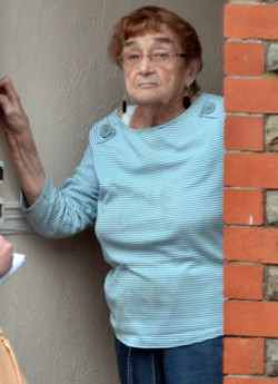 Picture of former Duncroft headmistress Margaret Jones, an elderly white woman in a blue and white striped T-shirt and blue drawstring jeans, standing at her door with a person in front of her taking notes