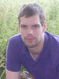 Mark van Dongen, a young white man with a short moustache and stubble, with matted light brown hair, wearing a purple T-shirt, crouching down on some grass.