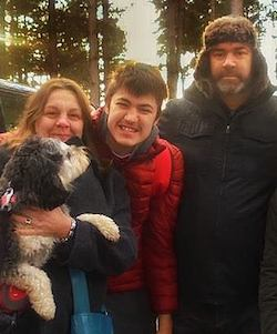 Matthew Garrett with his parents either side of him; his mother is holding a dog