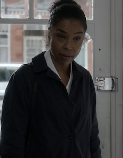 Picture of Maya Coppina (Sophie Okonedo), a light-skinned Black woman wearing a dark-coloured suit jacket with her hair tied behind her head in a bob, standing with her back to a front door on a London suburban street.