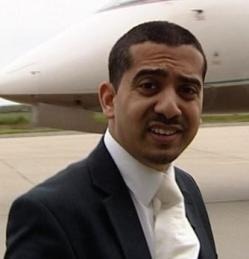 Picture of Mehdi Hasan, a light-skinned Asian man, wearing a suit with a black jacket, white shirt and cream tie.