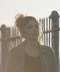 A picture of Mehreen Baig, a young South Asian woman wearing a black top with a jacket of uncertain colour over it, walking along a fence, with a low sun to the side.