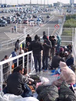 A picture of a group of migrants or refugees standing or sitting on a ramp behind a metal fench, behind which are several lanes of queueing cars, approaching the Calais ferry port