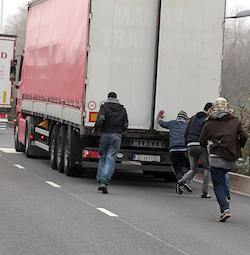 A 40-tonne articulated lorry pulled by a red Mercedes-Benz Actros tractor unit with a Serbian number plate and identity oval, a red curtain side and a white door with the name of the former owner 'Magazin Transport' still apparent. Four men are running after it so as to board from the back, where one of the doors appears to be partly opened.