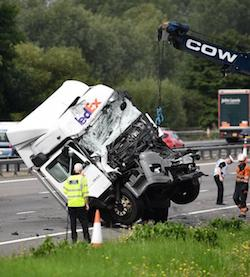 "A picture of a tractor unit with the Fedex logo being picked up by a winch attached to a blue mechanical arm with the word ""COW"" printed on it in white. The truck's front is very badly damaged, although the driver door is intact."
