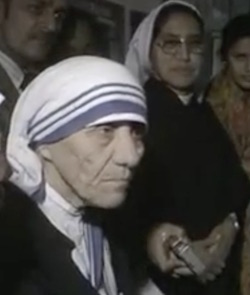 Mother Teresa, an elderly white woman wearing a white headscarf with blue stripes at the front, with an Indian woman wearing glasses and a white headscarf to her right.