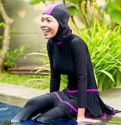A woman sitting on the edge of a swimming pool, wearing a black two-piece black swimsuit consisting of a tunic and trousers with pink decorative lines, with a black and pink hood over her head of similar material.