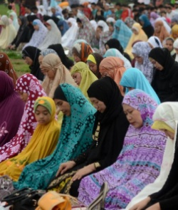 Image of Muslim women in various colour headscarves kneeling in prayer