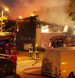 Picture of a burning building (the former Bravanese Centre in Muswell Hill, north London) with a fire engine and a white Ford Transit van in the foreground, with firemen trying to put the fire out