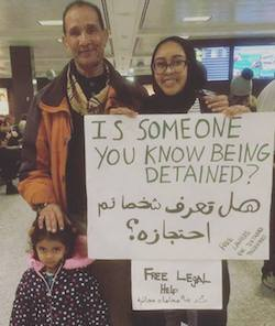 Nabra Hassanen and her father, a middle-aged man of Arab appearance, and a young girl in front of him in an airport departure lounge. Nabra is holding a sign which says 'Is someone you know being detained? Free legal help'