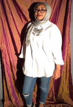Picture of Nabra Hassanen, a young woman with light brown skin, wearing thick, dark-rimmed glasses, a beige headscarf, a long, loose white over shirt with sleeves rolled up, and blue jeans with a tear at the right knee.