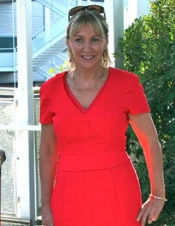 Picture of the MP Nadine Dorries, a white woman wearing a bright red dress