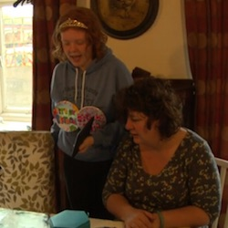 "Picture of a white teenaged girl wearing a grey jumper with a tiger motif on, with two badges saying ""Birthday Girl"" and a shiny tiara-like hair decoration, standing next to a middle-aged white woman with curly hair wearing a grey flowery top."