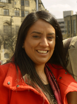 "Picture of Naseem ""Naz"" Shah, a middle-aged South Asian woman with long dark hair, wearing a red fleece jacket and a black T-shirt visible underneath. Licence: Creative Commons BY-SA 4.0"