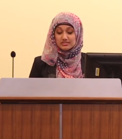 Nazma Khan, an Asian woman wearing a hijab, delivering a lecture