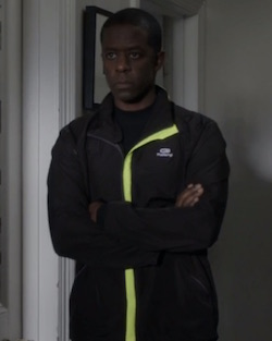 A still of a Black man wearing dark-coloured jogging clothes with a flourescent yellow strip along the zip