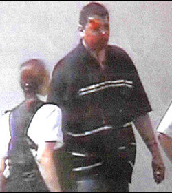 Nicky Reilly with a bloodied face, being led away by two police officers, one male (off picture) and one female, after the 2008 Exeter bomb blast