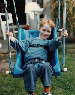 A picture of Nico Reed, a young white boy with ginger hair, sitting in a swing designed for a disabled user, with straps and a full seat, holding on to the support ropes with both hands. He is smiling. The swing is in a back garden with white plastic garden chairs on a patio behind, and a rear door to a house behind them.