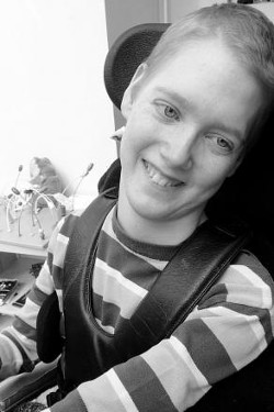 Picture of Nico Reed, a young white man with very short hair wearing a striped T-shirt, in a wheelchair with a leather harness, smiling.
