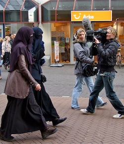 "A picture of two women in niqaab, one a dark purple scarf with matching face veil and one a navy blue scarf and veil, both wearing jackets over a long black abaya with visible leather shoes. Two women are facing them, one of them holding a large TV camera with two large grey microphones. The scene is a shopping street with an ""Arke"" shop behind them."