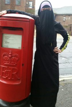 A woman in niqaab standing next to a red British postbox