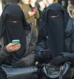 Two women wearing black niqaabs, one of them wearing black gloves on both hands, the other wearing a mitten on one hand and using a mobile phone in the other.