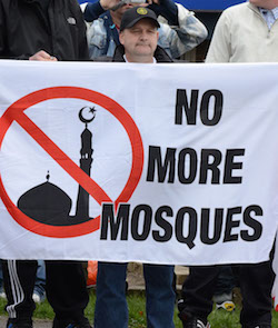 "An unnamed white man with a black cap with a cross-based emblem holding up a large sheet with ""No more mosques"" with a roadsign-like symbol showing a silhouette of a mosque in black with a red circle round it and a red line through it."