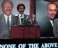 "Picture of Richard Pryor, a Black American male actor, standing at a podium in front of four microphones, in front of a simultaneous video of him speaking, with the slogan ""None of the Above"" below"