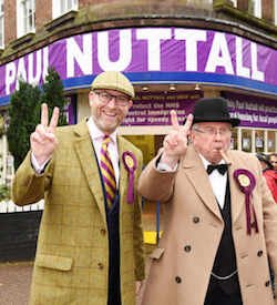 Paul Nuttall, a white man with a short beard, wearing a yellow and purple tartan cloth cap and jacket and a yellow and purple striped UKIP tie, standing next to Richard Gibbins, a shorter white man with glasses, wearing a black rimmed hat, cream jacket and a black and white tuxedo and bow tie underneath; both wearing UKIP rosettes, standing outside a converted shop unit on a corner with 'Paul Nuttall' displayed in big letters above the doorway along with posters showing UKIP promises.