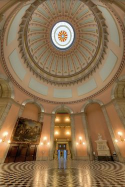 A wide-angle photograph of the inside of the Rotunda at the Statehouse in Columbus, Ohio. The picture is taken looking up into a dome which is topped with blue, yellow and orange stained glass and the dome is light orange with blue alcoves. At the bottom is a mosaic floor and there is a painting of what looks like a battle scene, with a US flag flying, on the back wall. Through an archway at the back you can see a staircase leading upwards on both sides, and past that, a door to the outside.