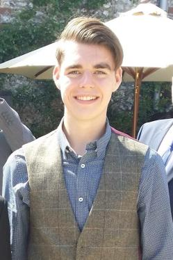 Picture of Oliver McGowan, a young white man with light brown hair combed from a parting on the left side, wearing a blue and white patterned shirt and a tweed waistcoat, standing in front of a large parasol.