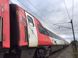 A British passenger train, painted red and white, with overhead wires which have been blown down by a storm