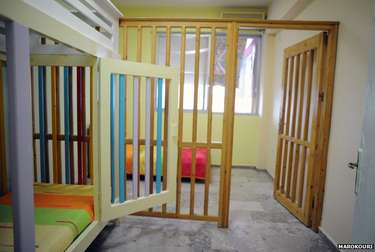 Brightly painted wooden cage-like cells, photographed in a care home in Greece