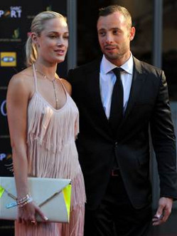 Picture of Reeva Steenkamp, a white woman in a light pink or peach colour dress holding an envelope in her right hand, and Oscar Pistorius, a white man wearing a black suit and tie.