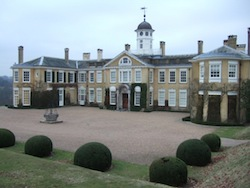 Polesden Lacey, an English stately home with yellow cladding and creeping plants over some parts of the exterior, and a small belfry above the middle section.