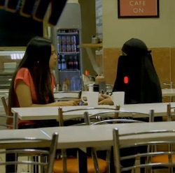 Poppy Begum and her friend 'Aisha', wearing a long black coat and face veil, in a London cafe at night