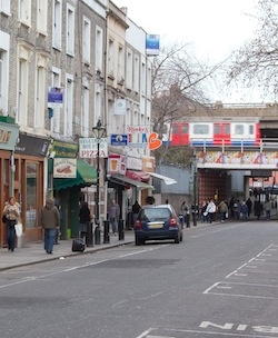 "Picture of a section of Portobello Road, west London, with a Tube train passing overhead and shops including Rinky's jeans, the Mau Mau bar and ""Vegtarian hot food and pizza"""